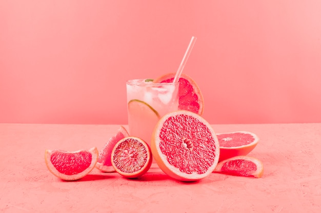 Halved grapefruits and glass of juice on coral background Free Photo