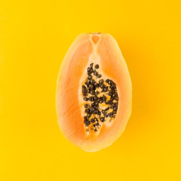 Halved papaya fruit on yellow background Free Photo