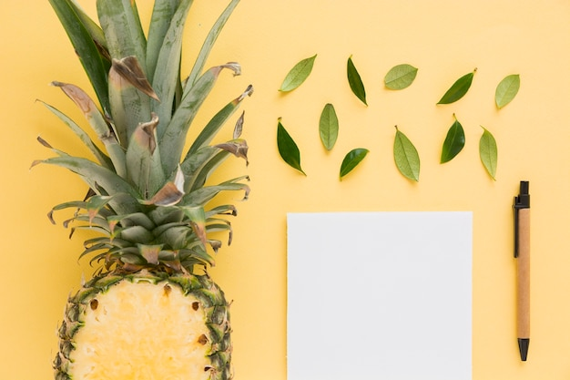 Halved pineapple with leaves; pen and white paper on yellow background Free Photo