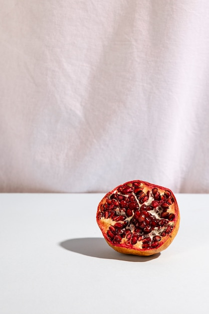 Halved pomegranate on desk in front of white curtain Free Photo