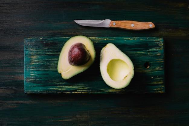 Halves of avocado on a cutting board flat lay Free Photo
