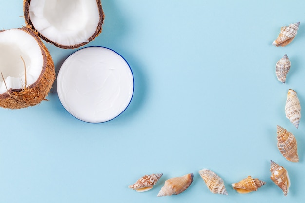 Halves of chopped coconut on blue background with seashells and cream jar Premium Photo