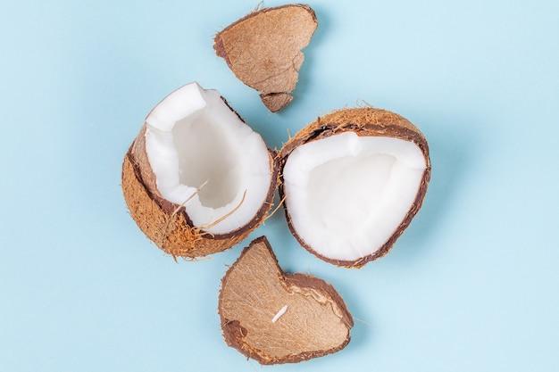 Halves of chopped coconut on blue background Premium Photo