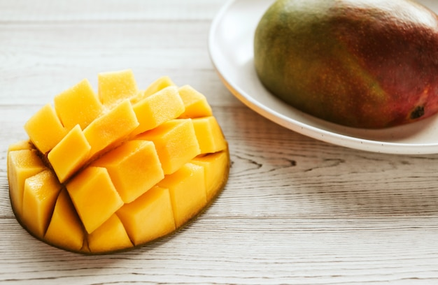 Halves of ripe mango on a white plate on a white wooden textured table copy space. Premium Photo