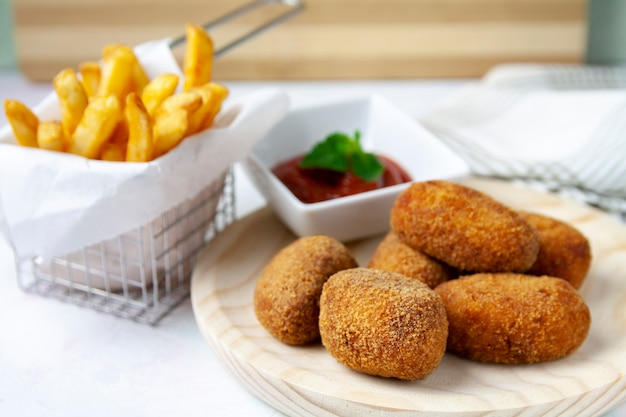 Ham and chicken croquettes with fried tomate and chips Premium Photo
