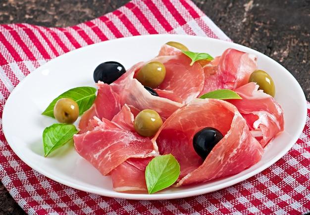 Ham, olives, basil on old wooden Free Photo