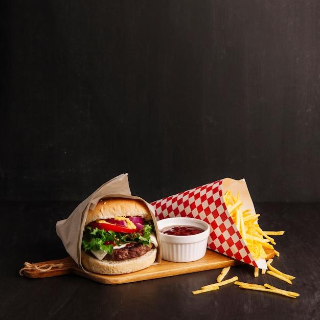 Hamburger next to chips Free Photo