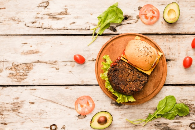 Hamburger on chopping board with spinach; tomatoes; avocado on wooden board Free Photo