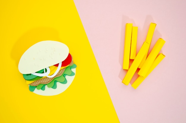 Hamburger and fries replicas on colored background Free Photo