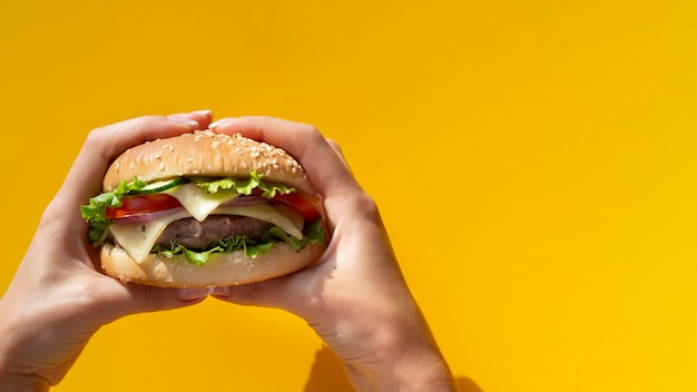 Hamburger held in front of yellow background Free Photo