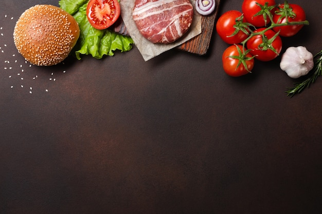 Hamburger ingredients raw cutlet, tomatos, lettuce, bun, cheese, cucumbers and onion Premium Photo