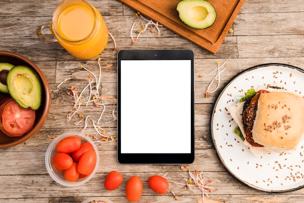 Hamburger; juice jar; tomatoes; avocado and sprout and digital tablet on wooden table Free Photo