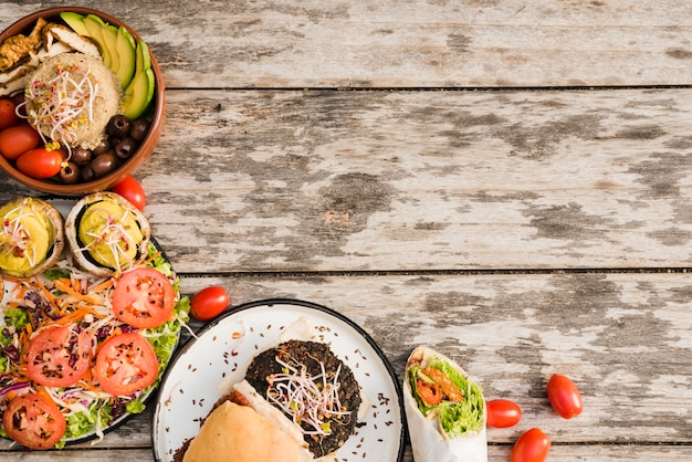 Hamburger; salad; burrito wrap and bowl with cherry tomatoes on wooden textured backdrop Free Photo