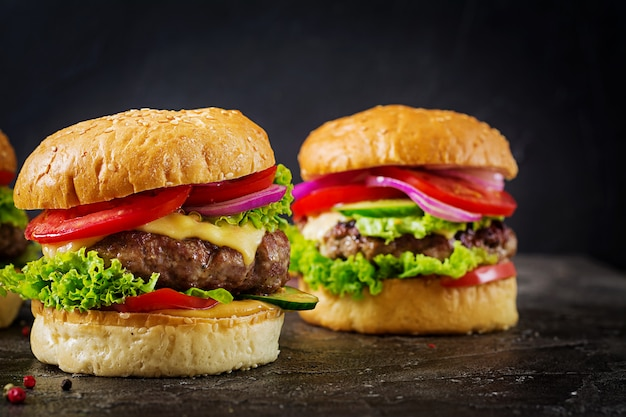Hamburger with beef meat burger and fresh vegetables on dark surface. Free Photo