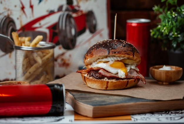 Hamburger with egg benedict and energy drinks can Free Photo