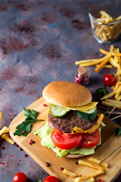 Hamburger with french fries, beer on a stone table Premium Photo