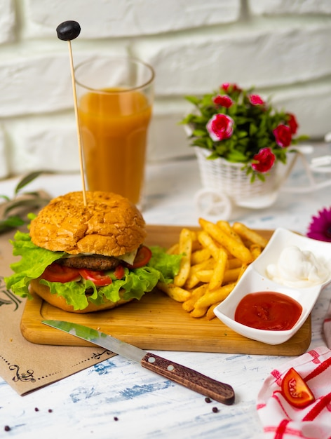 Hamburger with french fries on wooden board with ketchup and mayonnaise, kitchen Free Photo