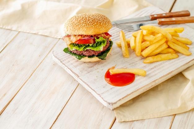 Гамбургер с картофелем фри и соусом на деревянной доске Бесплатные Фотографии