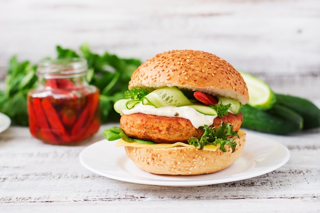 ジューシーなチキンハンバーガー、チーズ、キュウリ、チリ、タルタルソースの軽い木製のテーブルのハンバーガー Premium写真