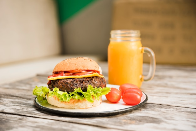 Hamburger with lettuce; tomatoes and cheese on plate with juice jar over the table Free Photo