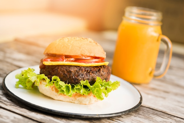 Hamburger with tomatoes; cheese and lettuce served with juice glass on wooden table Free Photo