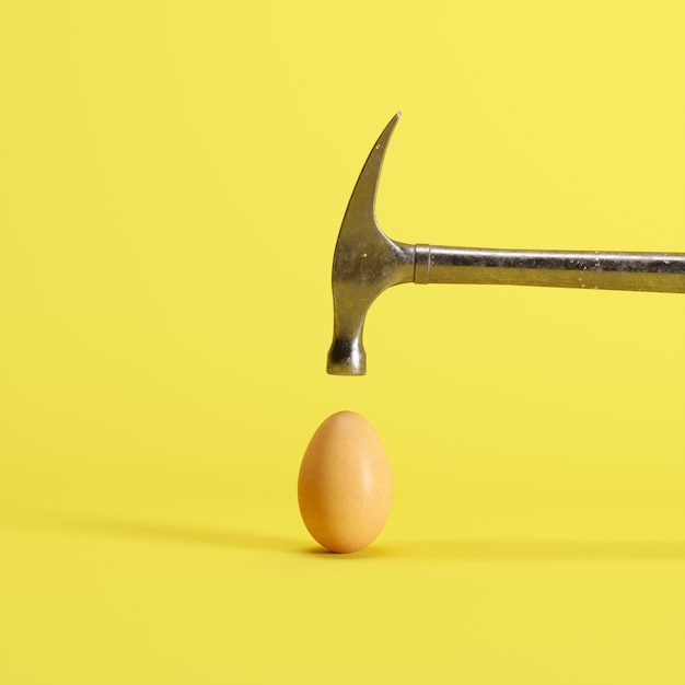 Hammer is hitting on an egg with yellow background Premium Photo