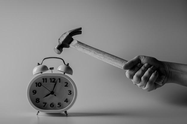 Hammer is smashing for destroy a alarm clock. fight and time limits concept. Premium Photo