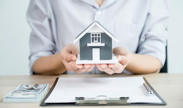 Передайте агенту по недвижимости, держите модель дома и объясните деловой договор, аренду, покупку, ипотеку, ссуду или страхование жилья. Premium Фотографии