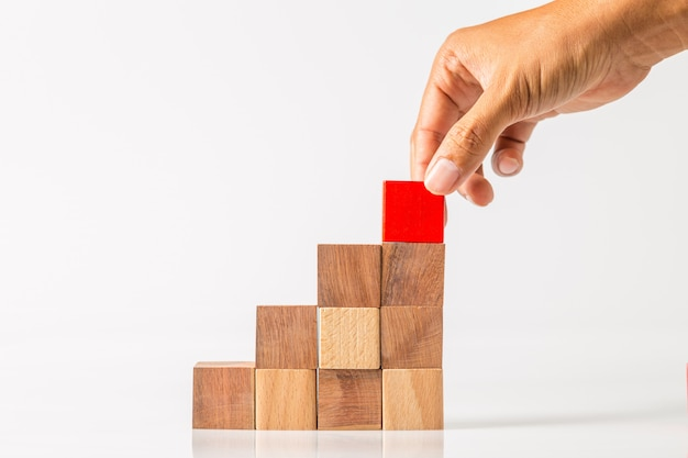 Hand adding the last missing wooden block into place. business success concept. Premium Photo
