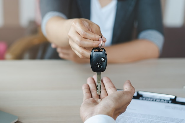 Hand of agent giving car key to customer after signed rental contract form. Premium Photo