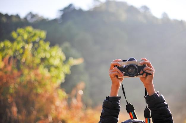Рука и камера фотографа в лесу. его любовь к фотографии и его камера. Premium Фотографии