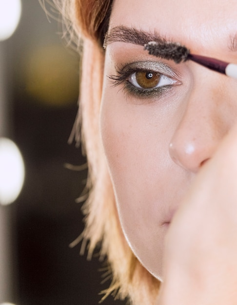 Hand applying eyebrow gel on woman Free Photo