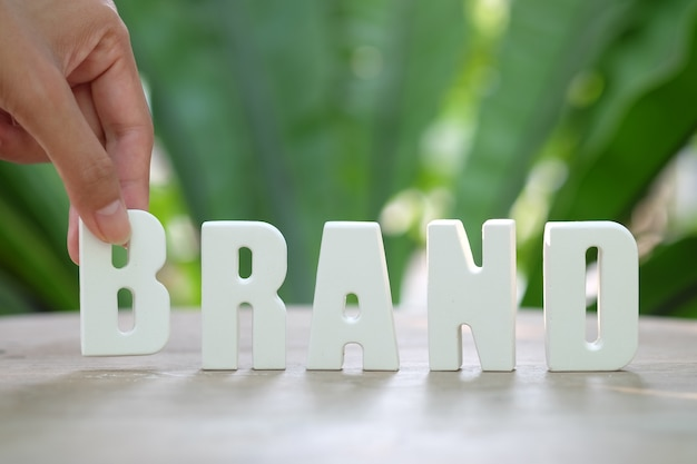 Hand arrange white letters BRAND Free Photo