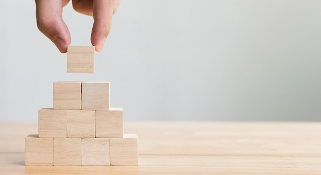 Hand arranging wood block stacking as step stair. business concept for growth success process Premium Photo