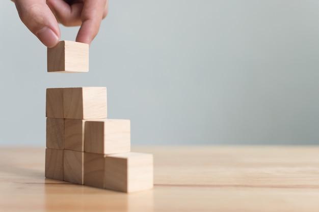 Hand arranging wood block stacking as step stair Premium Photo