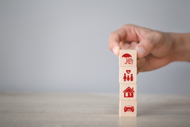 Hand arranging wood block stacking with icon insurance: car, Premium Photo
