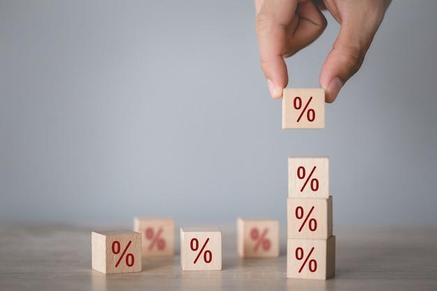 Hand arranging wood block stacking with icon percent symbol upward direction, Premium Photo