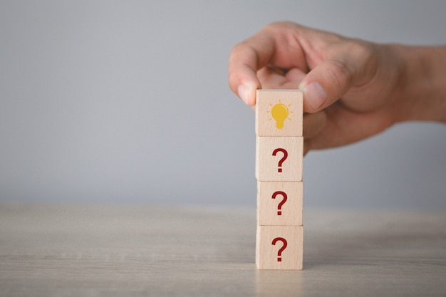 Hand arranging wood block stacking with icon question mark and lamp,thinking with question mark concept. Premium Photo