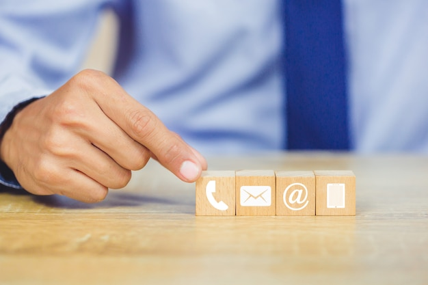 Hand arranging wood block stacking with icon telephone, mail, address and mobile phone Premium Photo