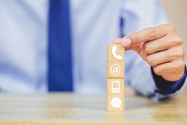 Hand arranging wood block stacking with iconl telephone, mail, address and mobile phone Premium Photo