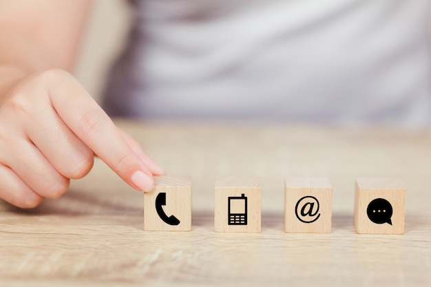 Hand arranging wood block stacking with iconl telephone, mail, address and mobile phone Premium Phot