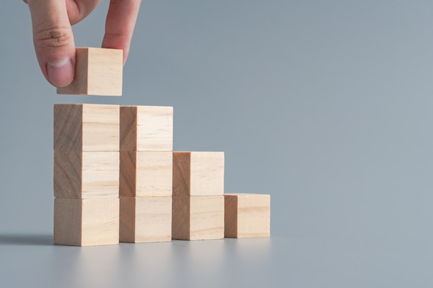 Hand arranging wood cube stacking as stair step shape, business growth and management concept Premium Photo