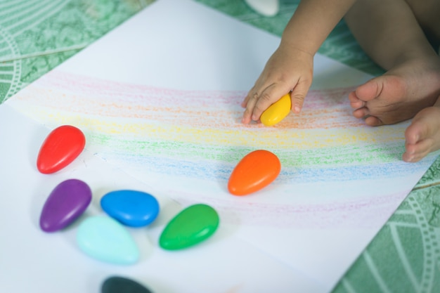 A hand of asian baby boy drawing lines and shapes with colorful crayons. Premium Photo
