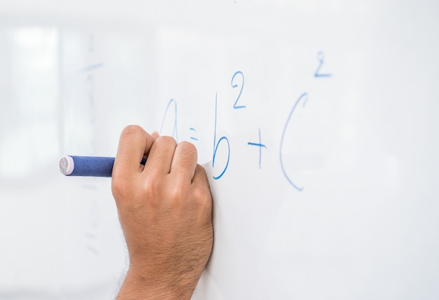 Hand asian solving solution math formulas, doing mathermatics problem on whiteboard in classroom at high school Premium Photo