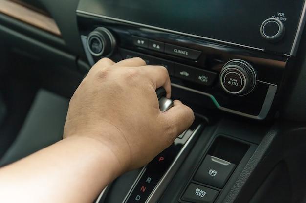 Hand on automatic gear shift, man hand shifting an automatic car, luxury car design interi Premium Photo