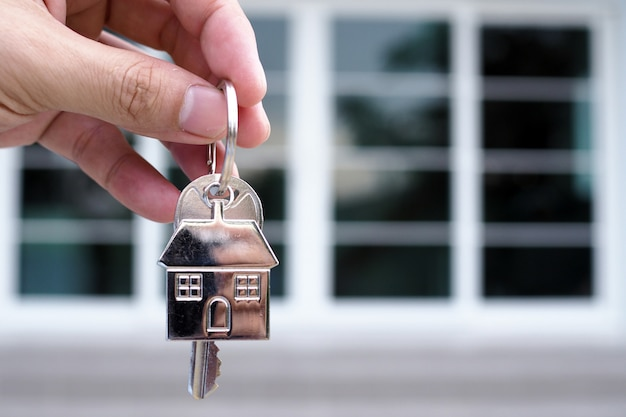 The hand of the banker holds the house key. home and land mortgage concept Premium Photo
