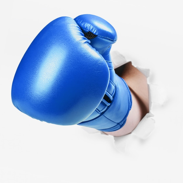 Hand in a blue boxing glove broke through the paper wall Premium Photo