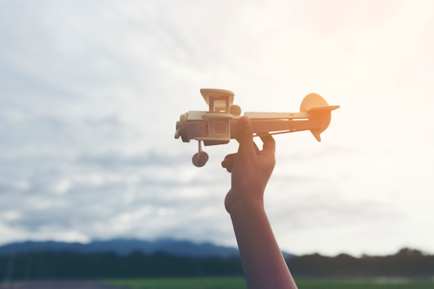 Hand boy with his hand runs the model of the plane into the sky storm cloud. Premium Photo