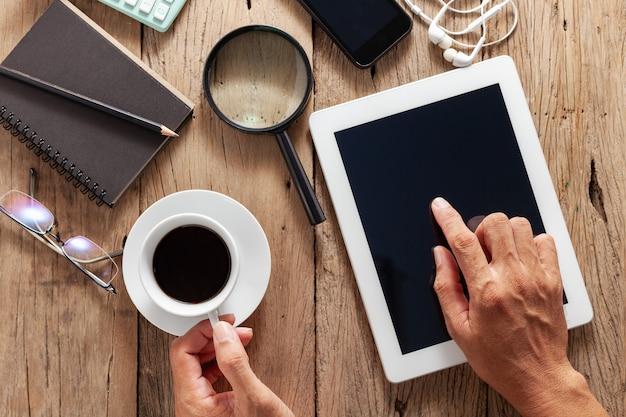 木製オフィスデスクとビジネスオブジェクトの使用タブレットで白いコーヒーカップを保持しているビジネスの男性を手します。 Premium写真