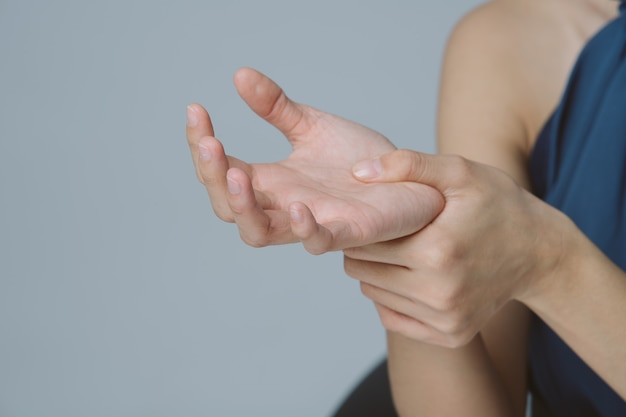 Hand of business woman holding her painful wrist caused by work